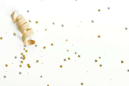 curled: a golden ribbon curled with sparkles of silver and gold stars on white background Stock Photo