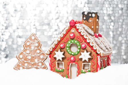 gingerbread: home made gingerbread house with a silver bokeh background