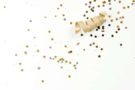 silver backgrounds: a golden ribbon curled with sparkles of silver and gold stars on white background Stock Photo