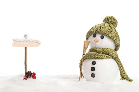direction sign: snow man with a sign in a artificial winter landscape