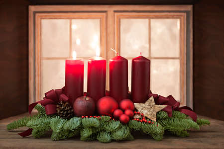 Advent wreath with red candles in front of a window Stock Photo