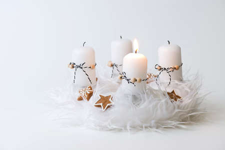 white advent wreath with decoration, one candle burning