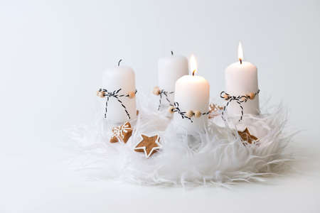 corona de adviento: white advent wreath with decoration, two candles burning