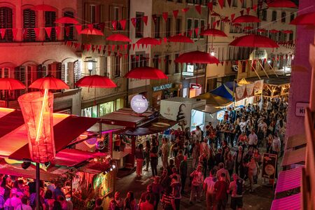 City Festival Brugg 24th of august 2019. street photography. Red umbrellas and bunting are hanging out in the street of old town with many people and spectators walking through the streets by night.