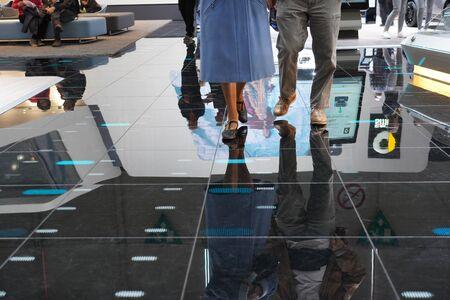 Visitors are walking around the exposition on reflecting black floor at Autosalon Genf 2019 in Geneva, Switzerland