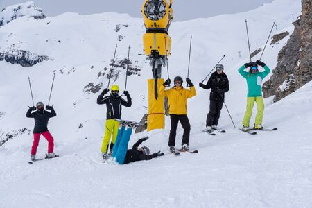 Young adults in winter, stand in line on a slope wearing skis, snowboard, helmet and goggles and holding sticks in the air with snow mountain in background on a cloudy day.