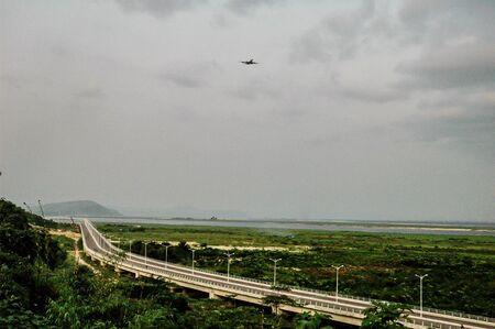 Airplane in cloudy sky over highway called Route de la Corniche from Mak? ? l? ? k? ? l? ? to Bacongo near Brazzaville in the Republic of the Congo.
