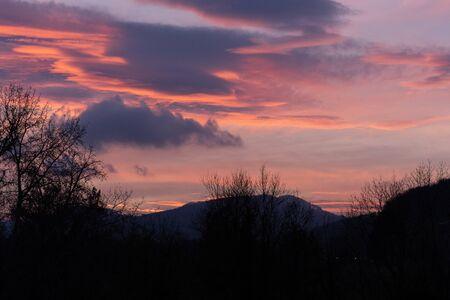 Coucher de soleil spectaculaire avec des nuages roses sur les bar-arbres et les collines en hiver sans neige. Photos non traitées et originales. En Suisse. Banque d'images