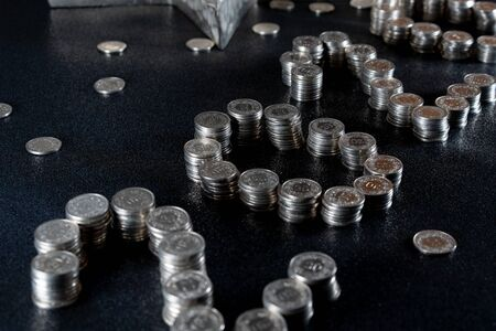 New Years 2020 graphic made from coins from Switzerland on a black shiny ground with silver star for concept. Concept for saving Money, cash and crisis in the new year. High angle view, close up. 版權商用圖片