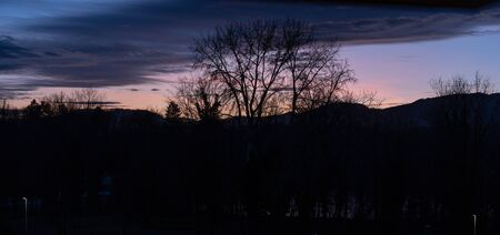 Dramatic sunset with pink blue clouds over bar trees and hills in wintertime without snow. Pictures unprocessed and original. In Switzerland. Banque d'images