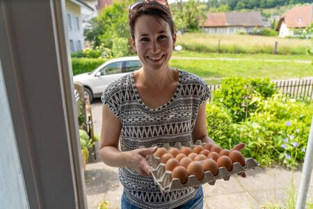 Beautiful young natural woman friendly smiling, delivers fresh brown eggs from free range chicken in egg box. Her car stands with open trunk in the street on sunny afternoon in Switzerland. High angle view. Stock Photo