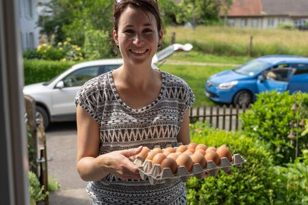 Beautiful young natural woman friendly smiling, delivers fresh brown eggs from free range chicken in egg box. Her car stands with open trunk in the street on sunny afternoon in Switzerland. Stock Photo
