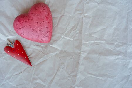Valentines day, little strawberry heart with pink flowered heart on white wrapping paper background. Close-up, place for text.