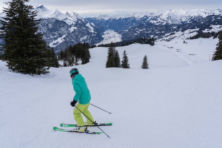 Young adults in winter, is skiing alone down the hill with helmet and goggles and holding sticks with snow mountain in background on a cloudy day.