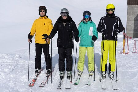 Young adults wearing skis, helmet and goggles, stand in line making a a strict face for fun, and holding sticks on a sunny day in wintertime.