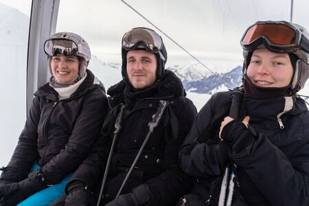 Young adults sitting in a cableway running up a slope, wearing helmet and goggles and holding sticks with snow mountain in background on a cloudy day in winter. Close-up.