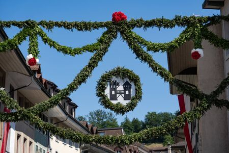 Old town of brugg after rutenzug, decorated with pine and paper flower and in the middle of the street hanging a coat of arm with the black tower of brugg on the 4th of july at Jugendfest Brugg 2019. Banque d'images