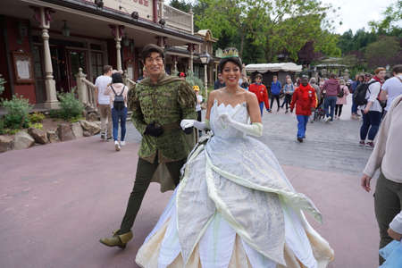 Actors of Kiss the Frog walk smiling as Tiana and the prince Naveen through the street of theme park in Disneyland. Paris France, 29. May 2019.