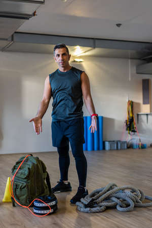 Gym instructor showing muscles. Motivated boot camp instructor stands with gym equipment in gym hall. Dumbbells, rope, sandbag on wooden floor. Portrait for gym concept.