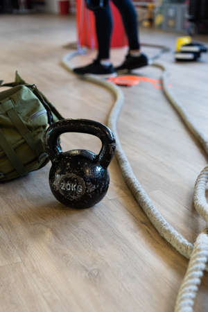 Gym equipment for boot camp and work out with kettle bell, rope, sandbag in gym hall on the floor. Instructor's legs in background. Vertical shot.