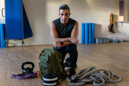 Motivated boot camp instructor kneeling with gym equipment in gym hall. Dumbbells, rope, sandbag on wooden floor. Portrait of lebanese instructor for gym concept.