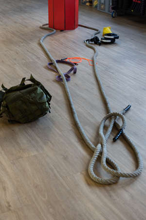 Gym equipment for boot camp and work out with kettle bell, rope, sandbag in gym hall on the floor. Vertical shot.