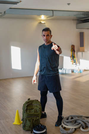 Gym instructor pointing at camera. Motivated lebanese boot camp instructor stands in gym hall. Dumbbells, rope, sandbag, mitts and yellow cone on wooden floor. Portrait for gym concept. Stock Photo