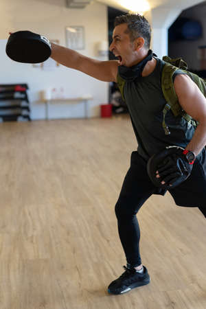 Motivated boot camp instructor stands with punch mitts in gym hall. Training with extended arm on wooden floor. Portrait for fitness concept. Stock Photo