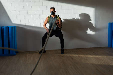Sportsman at rope workout with training mask. Indoor on oak floor with sun and shadow. For boot camp concept.