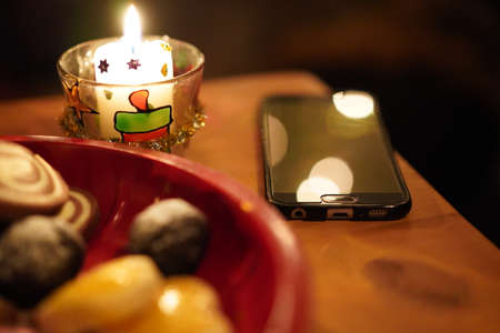 Black cellphone lying offline on a wooden table, with candlelight and pastry in a red plate on christmas eve. Blurry background for concepts.
