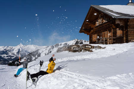 Two happy alpine skier and snowboarder throwing cheerful snow in air in front of Swiss chalet and blue sky. Hasliberg Switzerland.
