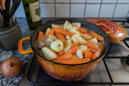 Orange casserole with meat, diced potatoes, carrots and celeriac on gas stove. Onion studded with cloves. Cooking scenery for concept.
