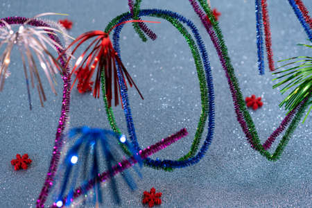2021 New Year postcard, sparkling colorful numbers. Pipe cleaners, whistle washer, sparkling turquoise background with red festive stars. Arts, abstract, creative, handmade. Concept for New Years Card