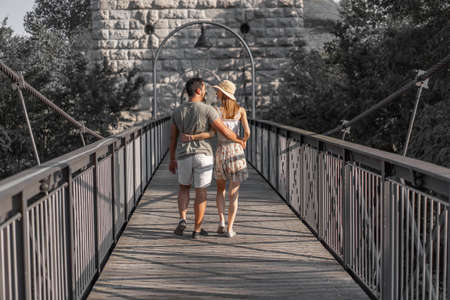 Rear view of young couple, walking embraced on wooden platform of hanging bridge of Aare river at late afternoon in September at sunset.