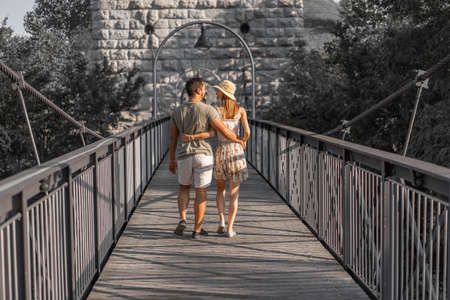 Rear view of young couple, walking embraced on wooden platform of hanging bridge of Aare river at late afternoon in September at sunset. Foto de archivo