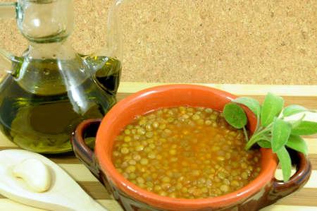 minestra di lenticchie con contenitore in terracotta con olio d