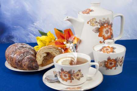 Tea with lemon croissant in fine antique porcelain cup
