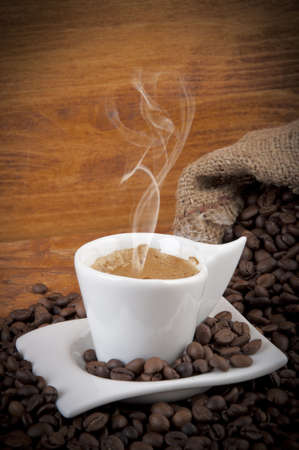 steaming hot cup of coffee with beans
