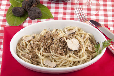 Spaghetti with black truffles with a plate full