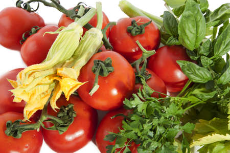 red tomatoes with squash blossoms and basil fresh seasonal vegetables