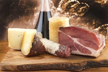 vinos y quesos: carnes y quesos con vino tinto en tabla de cortar de madera Foto de archivo