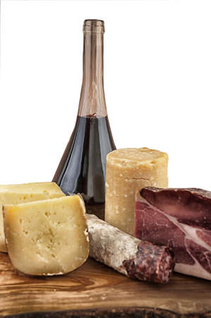 meats and cheeses with red wine on wooden chopping board photo