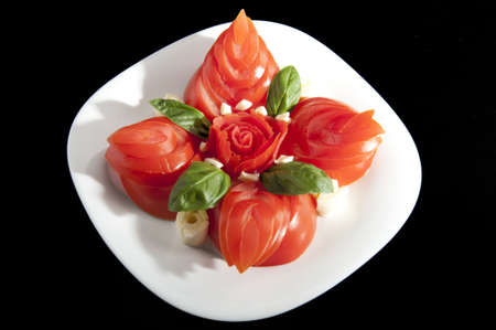 made of red tomatoes petal white plate with cheese photo