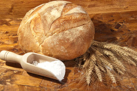 loaf of bread with slices and wheat ears photo