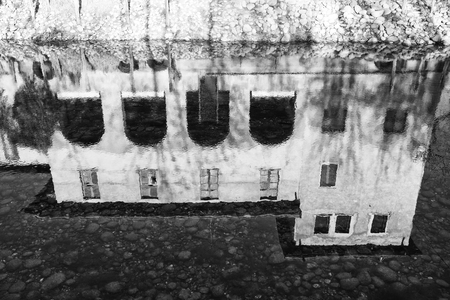 rock bottom: Black and White image of house reflection in water Stock Photo