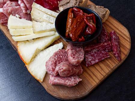 Rustic Tuscan tray with typical products: prosciutto (ham), brawn, finocchiona, crostini, salami, tuscan chilli and sliced pecorino cheese. San Gimignano, Siena, Italy