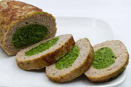 Baked meatloaf with spinach isolated on white background