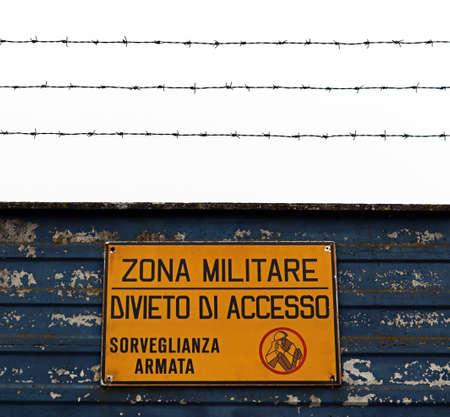 """Military area with yellow sign in Italian language: """"Military zone, no entry, armed surveillance"""". Translation: """"Military zone, no entry, armed surveillance""""."""