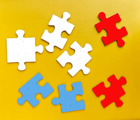 Colored pieces of a puzzle game on yellow background. Studio shot