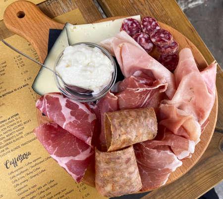 Rustic wooden serving tray with typical products of Italian Emilia-Romagna region: Prosciutto (Ham), Salami, Coppa di testa, ciccioli, sliced and Squacquerone cheese. Brisighella, Ravenna, Italy